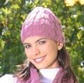 Женская розовая шапочка с косами, связанная спицами. Описание + схема